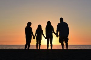sunset silhouette of family of four looking at beach
